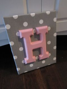 Use coral/peach patterned fabric to wrap around a mini canvas, then a wood stained letter in natural brown.