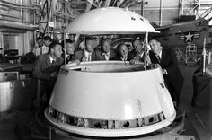 Gus Grissom, Deke Slayton, Gordon Cooper, John Glenn, and Scott Carpenter inspect an early design of a space program module.
