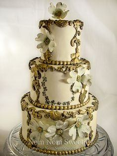 A wedding cake (faux) made for a bridal show adorned with gilded scrollwork, a touch of handpainting and handmade sugar dogwood flowers.