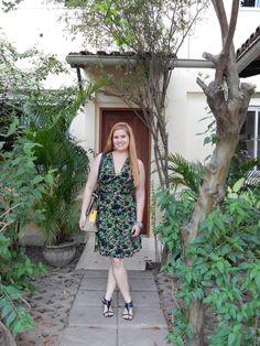 Look pra trabalhar fresquinha: vestido com estampa tropical, bolsa média bege e sandálias pretas.