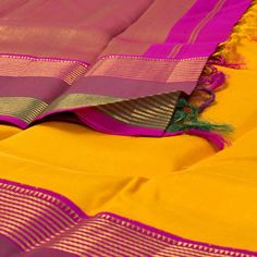 """This """"Yellow"""" #handwoven Kanjivaram Silk Sari from Bindu Giri is set off by a gold zari weaves Pink border on either side. An attractive gold zari adorn the pink pallu. The border is repeated on the pink blouse that completes the sari."""