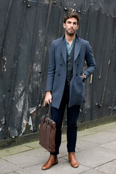 Stand out among other stylish civilians in a blue overcoat and deep blue jeans. Polish off the ensemble with walnut leather chelsea boots.  Shop this look for $552:  http://lookastic.com/men/looks/longsleeve-shirt-waistcoat-overcoat-jeans-tote-bag-chelsea-boots/4971  — Blue Chambray Longsleeve Shirt  — Charcoal Waistcoat  — Blue Overcoat  — Navy Jeans  — Dark Brown Leather Tote  — Walnut Leather Chelsea Boots