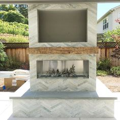 "Can you believe I miss work when I'm on vacation? But this is why! I'm pretty much obsessed with this fireplace at my modern farmhouse outdoor space. Herringbone slate, reclaimed wood mantle and a sleek fire insert is a winning combo. The space at the top is for their outdoor TV and will be covered by a ""frame"" that matches the mantle. Seriously so happy to see my vision come to life! #aneyeforpretty #exterior #outdoor #spaces #modern #fireplace"