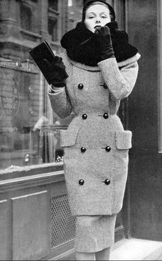 1950 Model in black and white tweed coat and skirt with large otter fur-lined collar and two large pockets by Jacques Griffe, photo by Pottier,