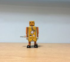 Vintage yellow wind-up tin toy robot  miniature toy for