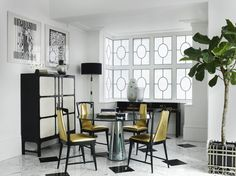 In a nook of a London home's breakfast area, a simple console accented with magnificent vases rests in front of a painted ironwork window. Tour the entire home.