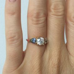 Custom engagement ring with an old European cut white diamond, bicolor pear cut sapphire, antique coral, and champagne diamond. Set in 14k yellow gold. Mociun