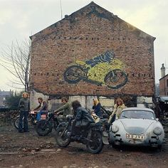 Kingston Racing Motors in Olinda Terrace, spring 1975.Is the man with the wrench a mechanic? Why is the woman with the clapped-out Porsche looking so naughty? Will James C Gallagher, whose business it is, always have his back to the camera? And after painting the wall, why did Barry have to leave Leeds? The council demolished the lot shortly after this snap .  Peter Mitchell