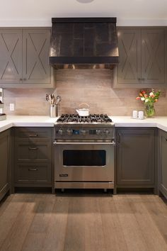 taupe kitchen cabinets + stone tiled backsplash + gray washed hardwood
