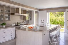 The eat-in kitchen, which is equipped with a Wolf range and Rangecraft hood, opens to a cutting garden. The custom-made island is sheathed in limestone by Exquisite Surfaces, and the barstools are by Janus et Cie.