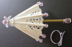 Parasol made from a doily, toothpicks, beads and a skewer. Really cute! Instructions with photos