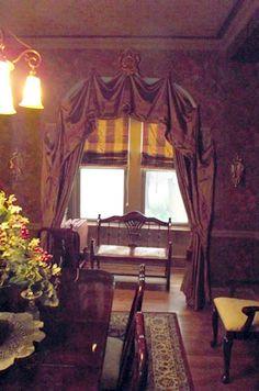 High Victorian Drape over a Dining room alcove.  Plaid gantt roman shades treat the alcove windows.Custom Drapery,Custom Window Treatments, Victorian Dining Room