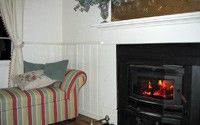 Herrmann's Cottage lounge room with wood fire burning