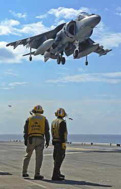 Harrier fighter jet hovering over aircraft carrier...