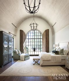 The 18-foot barrel-vault ceiling in the master bedroom is more dimensional thanks to antique-finished wooden boards. Judy Long, a decorator friend of Lisa and Michael, devised the solution for arched door shutters for privacy and to protect from harsh lighting.