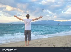 Man raising hands and open arms. Happy lifestyle man when sun rising up or sunset. Man, sea, sun, sky, clouds, mountains, ocean - the concept of the free way of life. Downshifting. Travel, vacation.