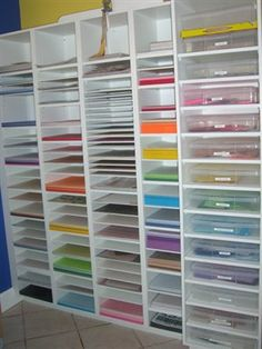 """Three columns for 12"""" x 12"""" paper,              one column for 8 1/2"""" x 11"""" paper,            one column 14"""" x 14"""" for scrapbook bins with hinged lids that hold scraps (one for every major color).  Divided card stock from patterned paper per color.  Also has space for specialized papers ---birthday, baby, etc."""