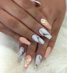 Matte acrylic nails in a marble and peach color with rhinestones