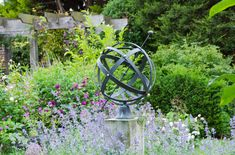 Beautiful iron sun dial acts as focal point in this English country garden ©  Marianne Majerus