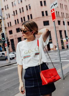 Carmen Hamilton, CHRONICLES OF HER wears Gucci logo t-shirt, denim skirt and Loewe red, chain bag