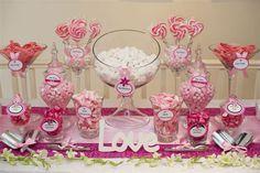 Mesa dulce de amor y amistad o de San Valentin decorada con caramelos de colores rosado y fucsia, además de chupetes. #MesasDulcesAmorYAmistad