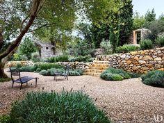 A garden featuring lavender bushes and carob trees   archdigest.com arden amid lavender bushes and carob trees.