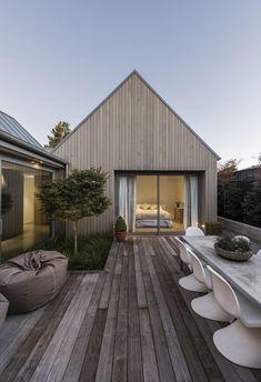 Terrasse moderne avec le revêtement bois et les lignes épurées de la façade et du mobilier.