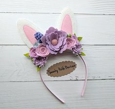 *LIMITED* listing for one gorgeous keepsake bunny ear headband made with 100% wool felt flowers, wool felt ears, silver glitter accents and bright green leaves. The flowers and ears are attached to a plastic satin covered headband in light pink. The headband measures 9.5 L x 6.5