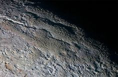 In this extended color image of Pluto taken by NASA's New Horizons spacecraft, rounded and bizarrely textured mountains, informally named the Tartarus Dorsa, rise up along Pluto's day-night terminator and show intricate but puzzling patterns of blue-gray ridges and reddish material in between