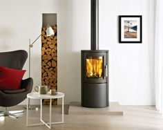 photo of modern warmth brown cylindrical stovax living room sitting room with alcove high efficiency fire wood burner and designer chair