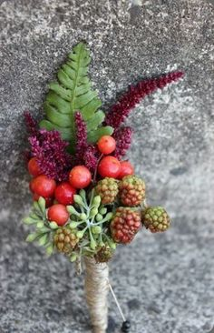 Boutonniere with berries and botanicals, perfect for an autumn wedding sophisticated florals