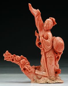 "A Chinese Antique Carved Momo Red Coral Figure: finely carved from the coral with Momo red tone as a figure standing in robes with a blooming branch beside him, of Qing Dynasty, weighing 440grams  Dimensions: H: 7-3/4""; W: 5-3/4""; Weight: 440 grams"