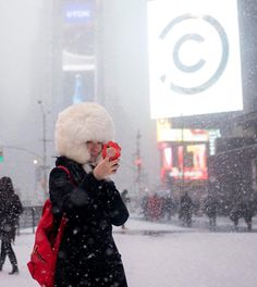 A female tourist from Japan takes a selfie during a snow storm in Times Square, New York, January REUTERS-Adrees Latif New York January, January 21, Times Square New York, Winter Storm, East Coast, Canada Goose Jackets, New York City, Winter Jackets, Shopping