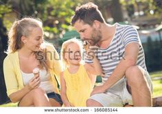 Close-up image of a young happy family spending their weekend in the park where the daughter feeding her father with the ice-cream  - stock photo