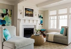 Fireplace Furniture Ideas. How to place furniture by fireplace. Transitional living room features a pair of matching gray settees facing each other across from a round woven coffee table. Living room boasts a framed flatscreen TV placed above a white fireplace mantle accented with a grey marble surround flanked by x stools topped with blue cushions and blue and grey abstract art. #fireplace #livingroom #Furniture Jennifer Palumbo.