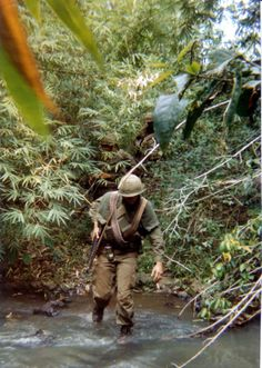 Crossing a stream with M60 ammunition over his shoulders and smoke grenades on his belt. ~ Vietnam War
