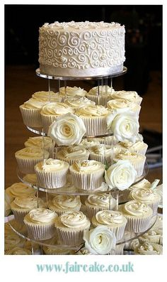 White rose cupcake tower with a layer of cake on top #wedding #weddingcupcakes #cupcaketower #white #rose