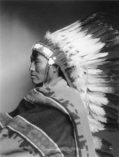 Shavehead, an Arapaho man sitting in profile and wearing a feather headdress and a blanket. This photograph was shot by Rose and Hopkins during Denver's Festival of Mountain and Plain circa 1896-1899