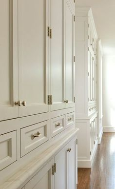 Tone of storage in kitchen with stacked cabinets accented with polished nickel hardware.