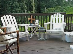 A pair of white Adirondack chairs with pillows and a vintage fan make the back deck a cozy space to relax outside.