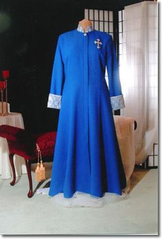 Tradition with a flare. Enjoy the elegance of fit with fashion! Princess style female clergy robe accompanied by accents of ecclesiastical brocade on collar, cuffs and three back pleats. Robe shown in royal blue with blue/silver accents. Fully lined.