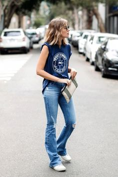 Carmen rocks a wavy long bob with bangs, a vintage tee, Saint Laurent clutch, flared jeans and white sneakers.
