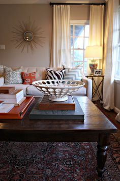I can't decide what I like more. 1)the white bowl 2) the coffee table or 3) the sun/gold/mirror hanging on the wall.