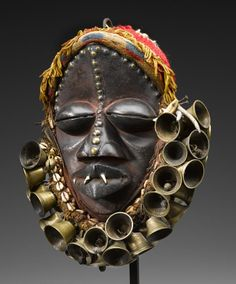 Africa | Mask from the We people of Liberia or Ivory Coast | Wood, fiber, bells, brass, shells, teeth and pigment | ca. 1970
