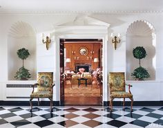 Boxwood topiaries grace shelled alcoves in the black-and-white marble-tiled gallery, while two antique chairs that came with the house frame a view of the wood-paneled library.