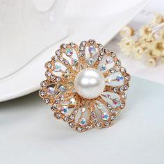 Elegantná zlatá brošňa s bielou perlou a kryštálikmi s prepracovaným dizajnom