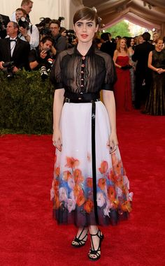 2015 Met Gala: Lily Collins is wearing a Chanel creation! The outfit consists of a black sheer short sleeve button up blouse and a white wrap skirt with flowers on the bottom. She is also wearing a netted head pieces. Lily nails it! The dress is classy and beautiful! The skirt is absolutely gorgeous! I love this from head to toe.