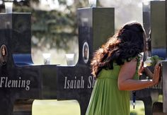 Friend Barbara Guedeney kisses the cross dedicated to Columbine victim Lauren Townsend at Chapel Hill Memorial Gardens in Littleton, Colo., on April 20.