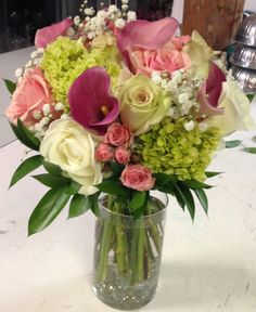 Pink calla lilies, roses, spray roses, mini green hydrangea, baby breath, & tah ruscus bouquet by All Grand Events