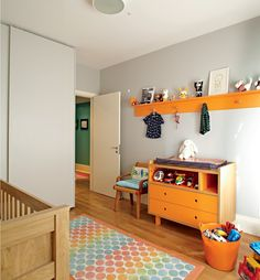 Quarto do filho de Marina Sanvicente. A arquiteta Bruna Riscali sugeriu tons fortes para a marcenaria. Daí os móveis laranja no quarto de Ravi, 2 anos. Mesmo com as paredes brancas, o ambiente é alegre e vibrante. O tapete de bolas e o cesto de brinquedos completam a decoração colorida.
